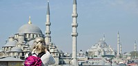 Woman photographs the Yeni Camii, The New Mosque or Mosque of the Valide Sultan located in the Eminönü district of Istanbul, Turkey.