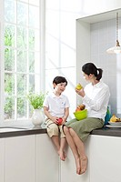 Mother and son sitting on kitchen counter