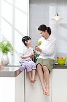Mother and daughter sitting on kitchen counter
