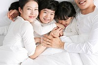 Family lying on bed