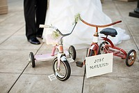 Vintage pink and red tricycles parked together with a sign reading ´just married.´ Out of focus bride and groom implied in background.