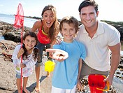 Portrait of smiling family holding small crab on sunny beach