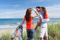 Family with blanket standing in grass on beach