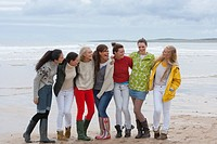 Smiling young women standing in a row on beach