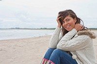Smiling young woman sitting on beach