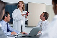 Scientist explaining molecular model to business people in conference room