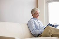 Caucasian man sitting on sofa reading book