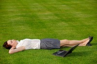 Businesswoman lying in park with laptop