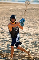 A lacrosse player training and practicing on the beach