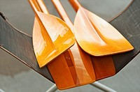 Detail of wooden boat oars on a dock at a lake
