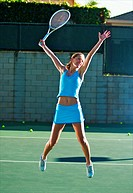 A female tennis player jumping in the air to celebrate winning