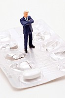 Figurine of businessman standing on top of medicine