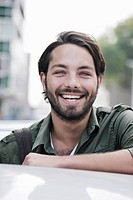 Germany, Cologne, Young man near car, smiling, portrait