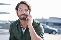 Germany, Cologne, Young man on phone, smiling