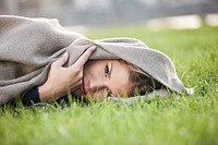 Germany, Cologne, Young woman lying in grass, portrait
