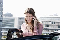 Germany, Cologne, Young woman on phone near parking lot, smiling (thumbnail)