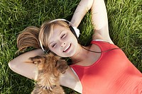 Germany, Cologne, Young woman with dog lying in grass, smiling