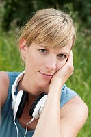 Germany, Munich, Mid adult woman with headphones, smiling, portrait