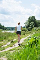Germany, Bavaria, Mid adult woman jogging near Isar river