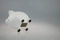 White Piggy bank on its side with Coin slot open showing piggy b