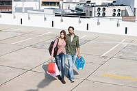 Germany, Cologne, Young couple with shopping bags, smiling