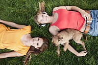 Germany, Cologne, Young woman lying in grass with dog, smiling, portrait