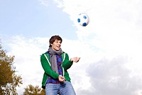 Germany, Cologne, Young man playing with soccer ball, smiling