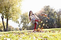 Germany, Cologne, Young woman playing in park with leaves, smiling