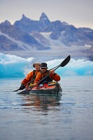 Men rowing canoe on still glacial sea