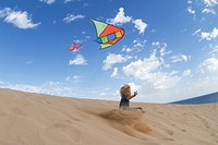 Boy flying kite on sand dune