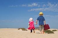 Siblings walking together on beach