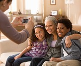 Woman taking photograph of grandmother and grandchildren