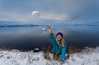 Woman throwing snowball by lake