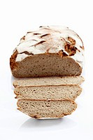 Rye bread loaf with slice on white background, close up