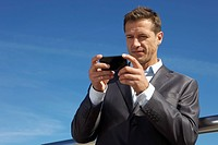 Germany, Bavaria, Munich, Businessman using cell phone (thumbnail)