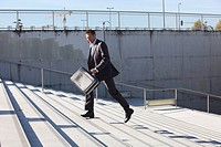 Germany, Bavaria, Munich, Businessman walking on stairs with briefcase, smiling (thumbnail)