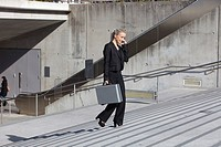 Germany, Bavaria, Munich, Businesswoman on stairs with briefcase and talking on cell phone, smiling