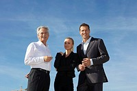 Germany, Bavaria, Munich, Business people standing against sky, smiling, portrait