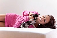 Young woman with chihuahua on bed