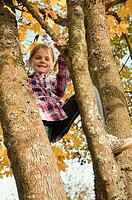 Germany, Bavaria, Girl climbing tree