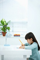 A girl writing on a book in front of the desk