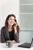 Businesswoman using cell phone at desk