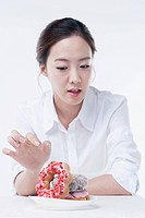 The woman trying to eat the doughnuts