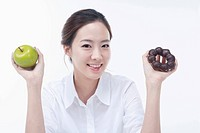 The smiling woman with an apple and a doughnut on each hand