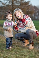 Germany, Upper Bavaria, Grandmother and granddaughter blowing bubbles