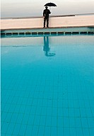 one man only at empty swimming pool under umbrella, clouded sky, after season symbol