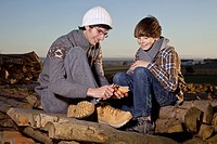Germany, Bavaria, Father and son sitting on wood with apple, smiling