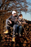 Germany, Bavaria, Father and son sitting on wood and cutting stick