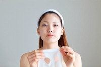 Young Woman Holding Facial Mask