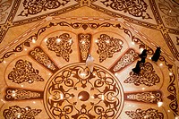 People walk on marble floor of atrium in Emirates Palace hotel, Abu Dhabi, United Arab Emirates